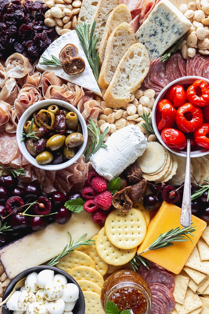 Image of a tray of charcuterie, cheese, nuts and olives
